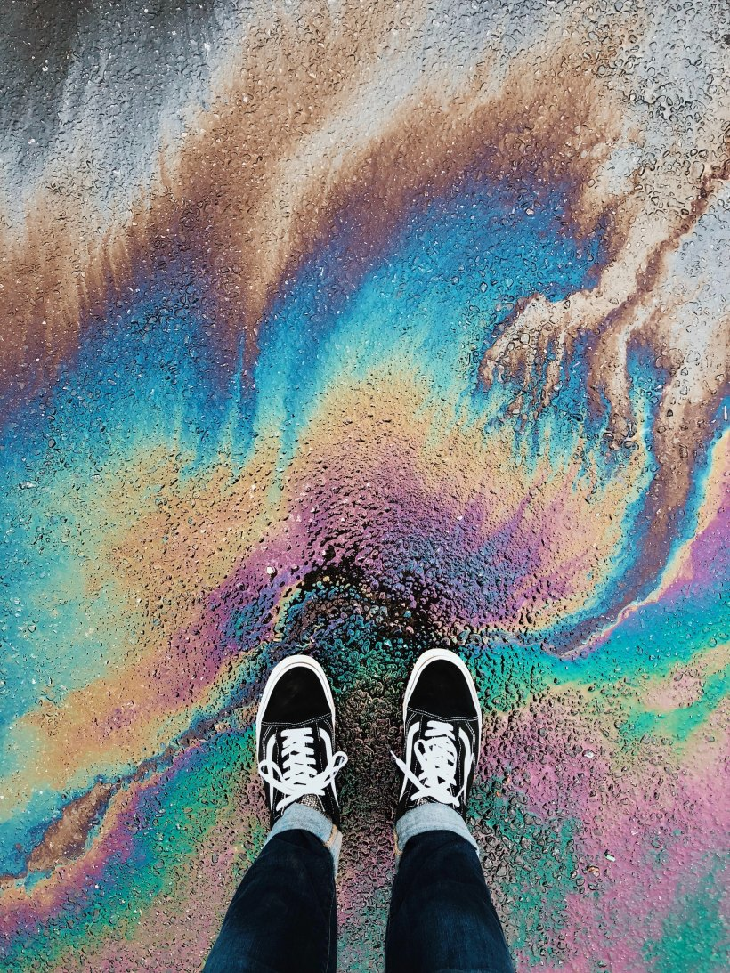 photo of black sneakered feet standing on rainbow oil spill