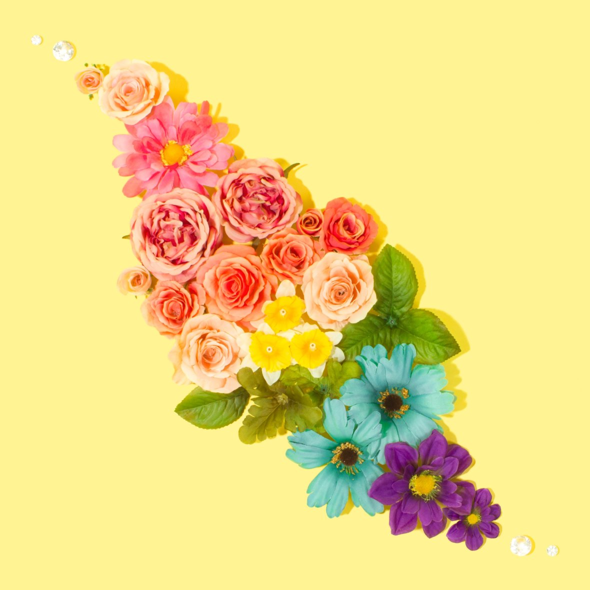 A variety of flowers arranged in rainbow colours from pink, red, yellow, green, blue to purple. The flowers are arranged in a diamond shape on a yellow background.