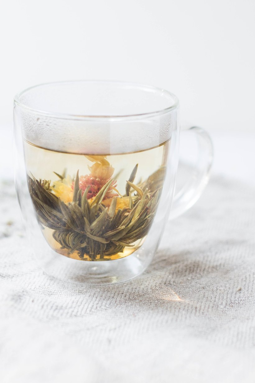 Photo of a clear tea cup with a blooming flower tea