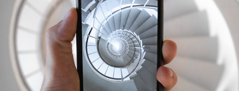 Photo of a hand holding a black smartphone, taking a photo of a white winding staircase from up above