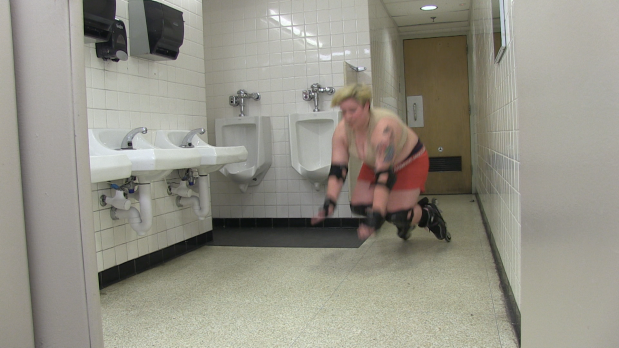 Photo of a person wearing roller blades mid-fall in a white bathroom
