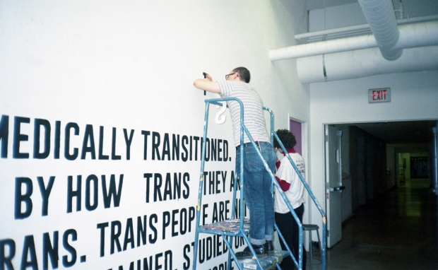 Photo of a person on a ladder painting a mural in black text on a white wall.