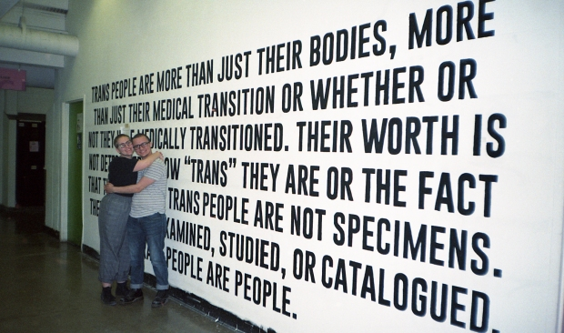 Photo of the two artists Kat and Samuel hugging in front of their mural/installation art piece, black text written on a white wall.
