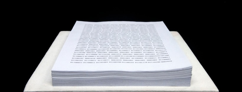 Photo of a text installation featuring binary code printed onto a stack of letter size paper.