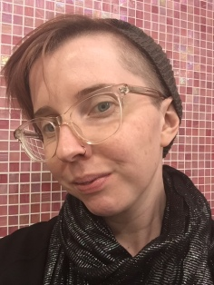 Photo selfie of a person looking into the camera wearing a grey beanie, clear glasses and a glittery black scarf