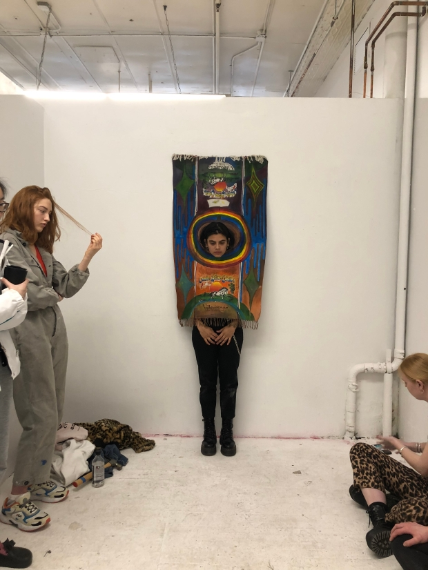 Photo of the artist standing in front of a white wall with head poking through a coloured painting.