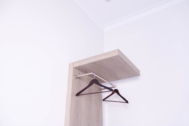 brown wooden frame with two brown coat hangers