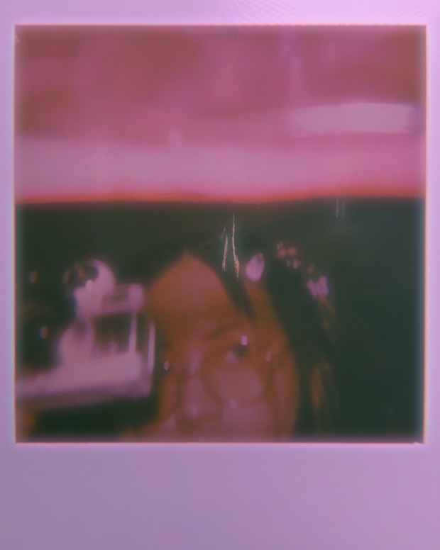 Blurry pink washed polaroid of a person's face holding a camera