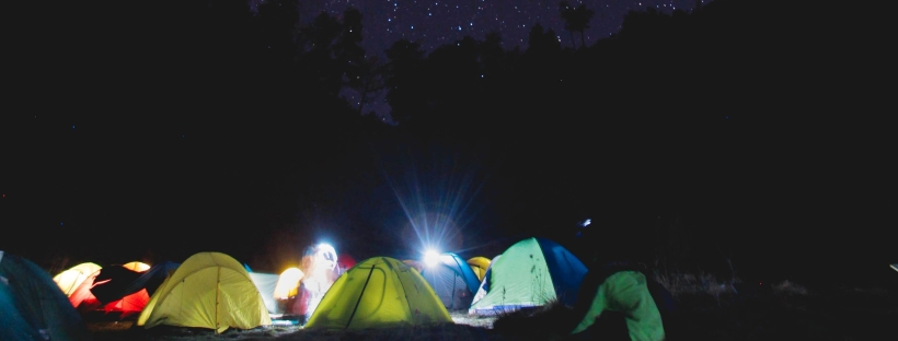 Photo of many coloured tents under a night sky