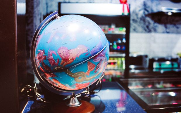 Photo of a blue globe with zodiac signs on a desk