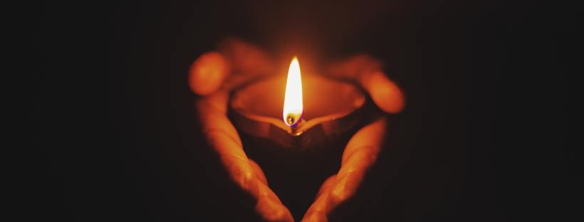 Photo of obscured hands holding a candle