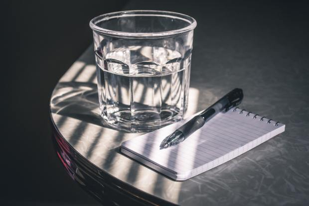 photo of a glass of water, notebook and pen on a table in the sun