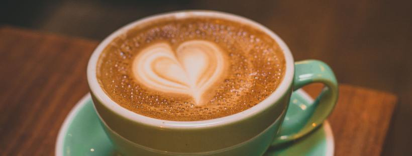 Photo of a green coffee cup and saucer sitting on a brown table, the top of the coffee foam is in the shape of a heart