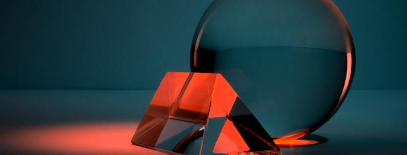 Photo of a see through sphere leaning against a triangular shape, the colour scheme blue and red