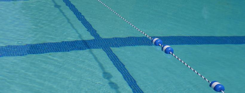 Photo of a blue chlorine swimming pool with blue lap lanes.