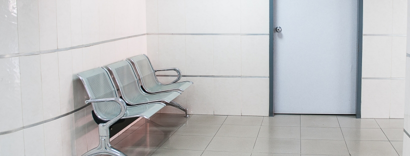 Photo of a white washed waiting room with plastic chairs, a door and a painting on the wall
